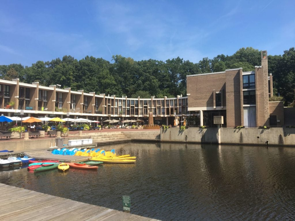 Lake Anne Village Center is shown, a U shaped development with restaurants and shopping. The lake is pictured with rental canoes. Reston, VA.