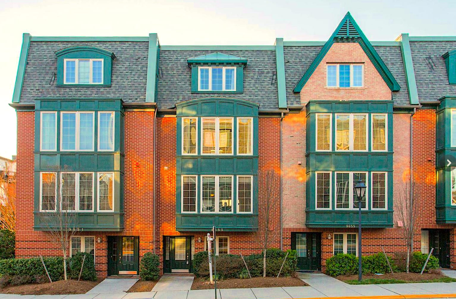 Tudor style townhomes with red brick and green trim at Beech Grove