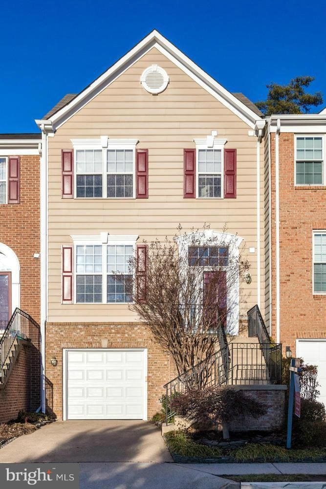 A townhome in Springfield with a 1 car garage and vinyl and brick siding