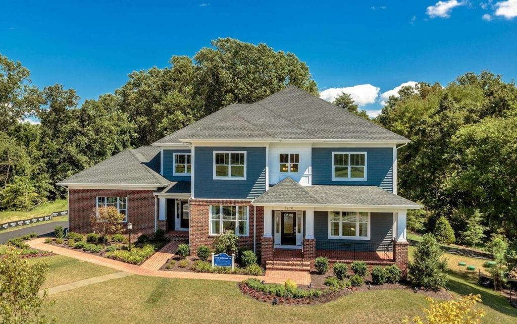 An elevated shot of one of many new homes in Fairfax VA. Blue siding, brick, beautiful landscaping.