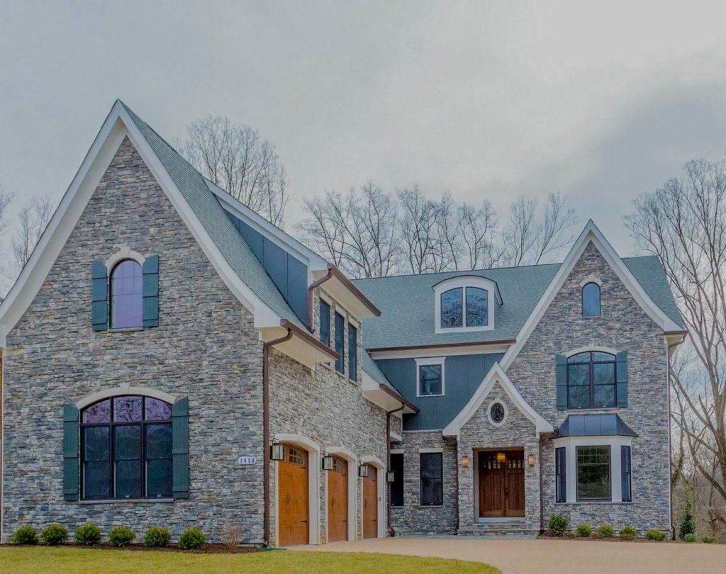 A large, stone front new home in Northern VA. Three car side garage and pointed tutor style architecture.