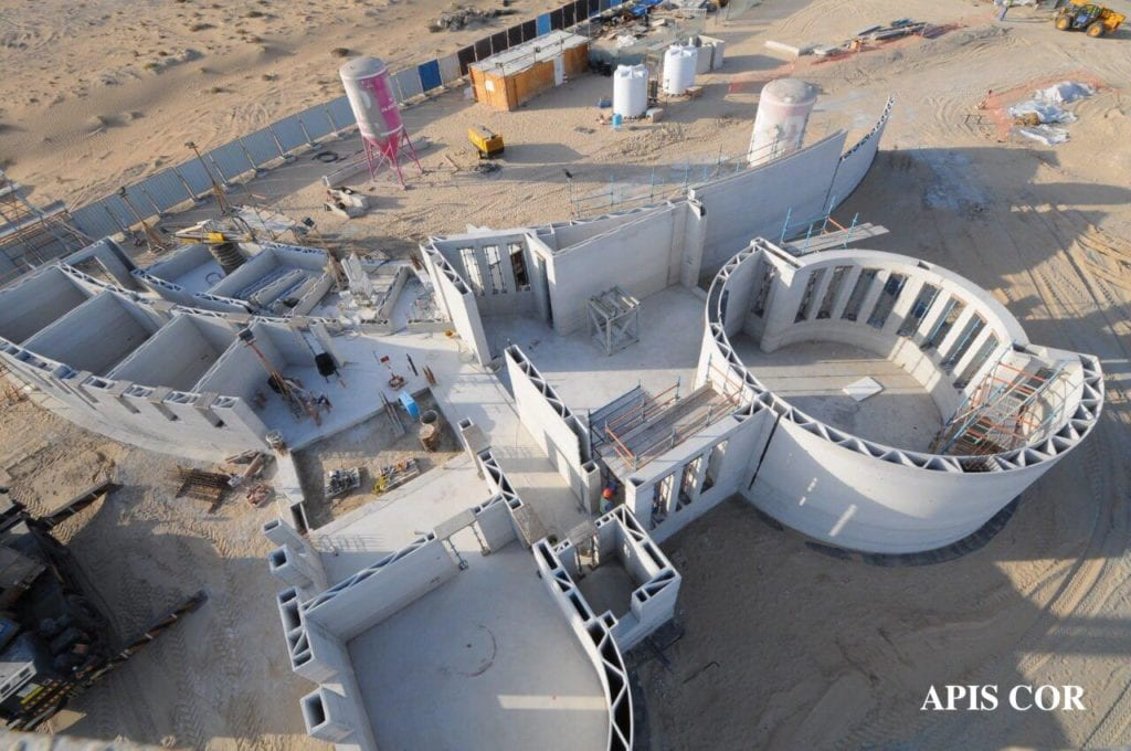 A home that is under construction, built by a 3d printer. Rooms are circular, square and other hybrid shapes. Gray in color, and surrounded by desert in the background.