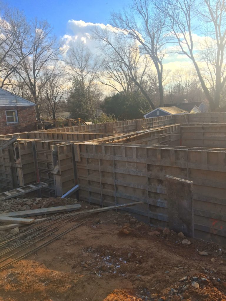 Foundation about to be poured in a new home in Northern VA. The forms look like small walls that will hold the foundation concrete in place. Wintertime, in the background you can see trees without leaves.