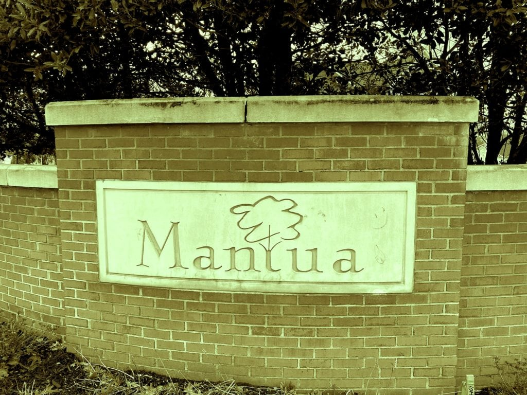Entrance to the Mantua neighborhood, a brick and stone sign carved with a neighborhood logo.