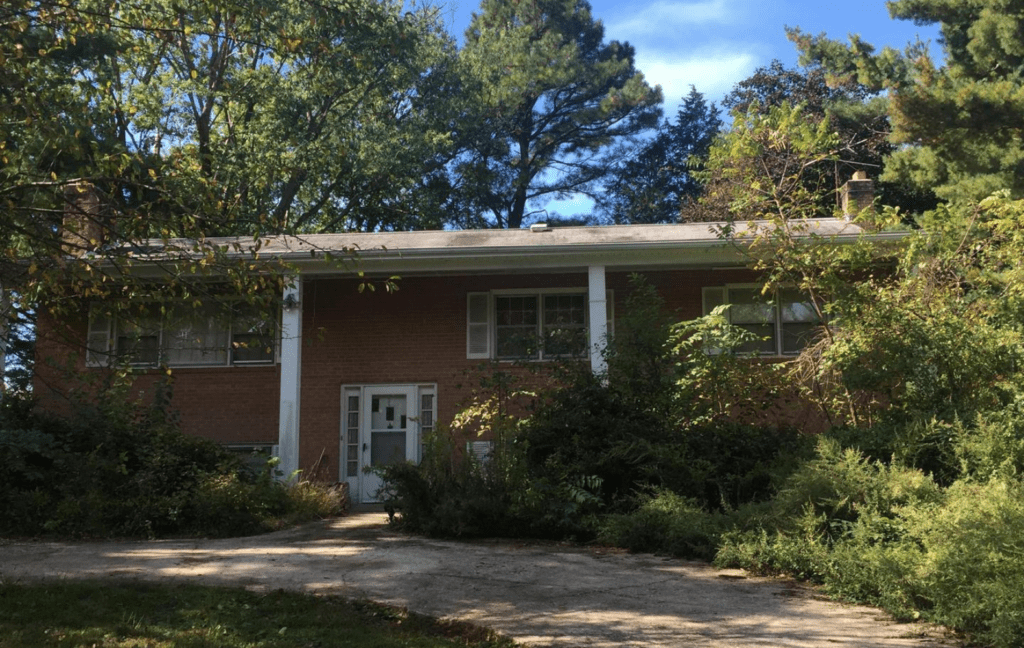 A home that needs extensive remodeling and landscaping. This home is located in Great Falls VA. You can see overgrown trees and shrubs in the front of house.