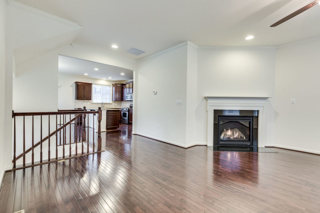 A vacant townhome in Chantilly VA. Dark floors, a gas fire log on and kitchen in the background.