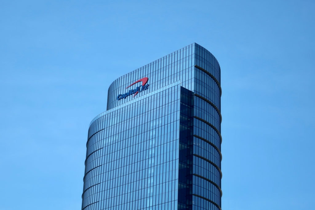 """A large glass building is seen on clear day with blue skies. The building has the """"CapitalOne"""" logo on the top."""