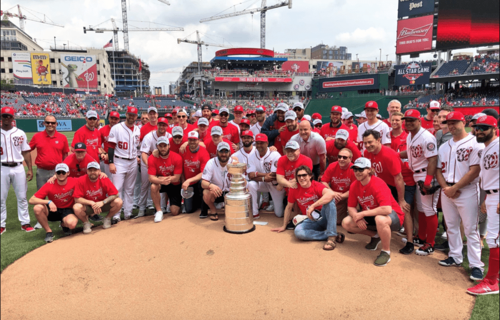 A large metallic trophy on the mound of a baseball field. Surrounded by the Nationals baseball team and Capitals hockey team.