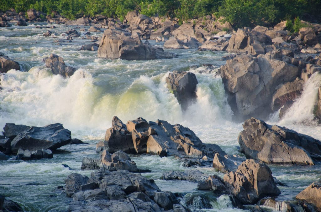 Rapids are shown rolling over large rocky outcrops of a river. Dangerous looking white water.