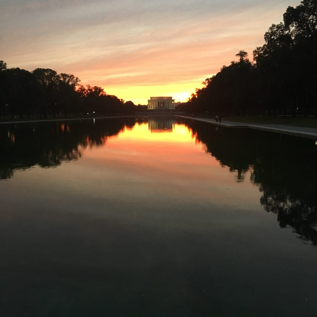 A sunset over a memorial and reflecting pool. Trees and the sun rays can be seen in the reflecting pool.