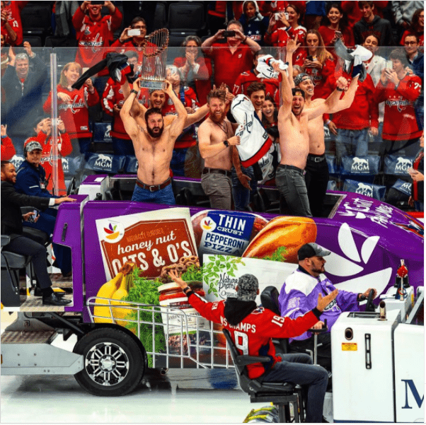 Shirtless members of the Nationals baseball team are pictured riding the zamboni at intermission of a Capitals game. Fans look on and cheer.