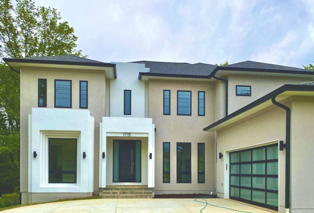 A large modern home is shown, with lots of windows, light colored stucco and cement for the structure. Frosted glass garage.