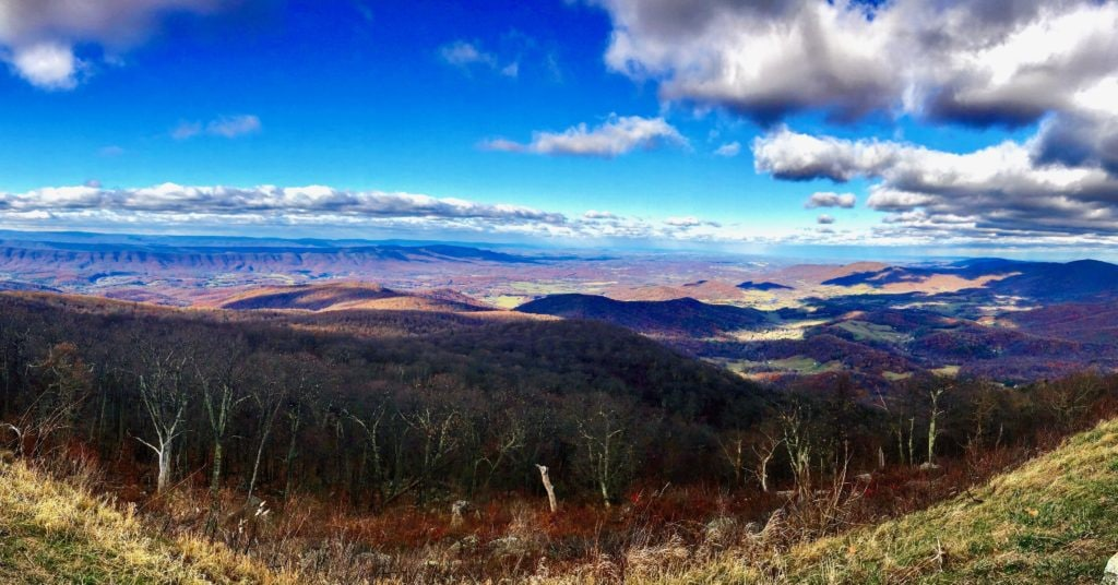 A panoramic view of blue skies over a far off mountain range and forest with trees and leaves that are changing color.