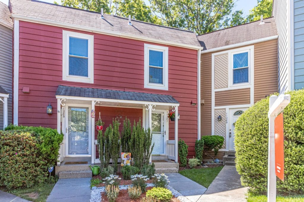 Three townhomes are seen, two are part of a duplex with red siding, and another with brown siding and some shiplap