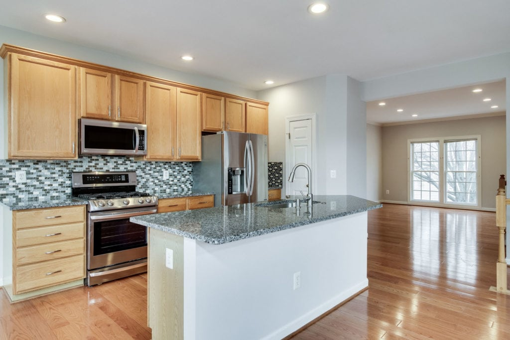 Kitchen with granite counters, glass tile backsplash, stainless appliances and lots of recessed lighting.