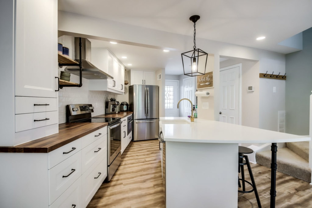 A renovated kitchen with white cabinets and dark handles, butcher block counter, a white quartz island and brass faucet. Brown flooring is seen also.