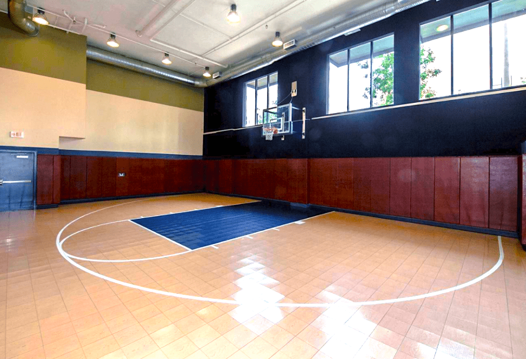An indoor basketball court at a condo community. Blue and tan floor with a separately mounted basketball hoop on the wall. Condos usually have more amenities than townhomes.
