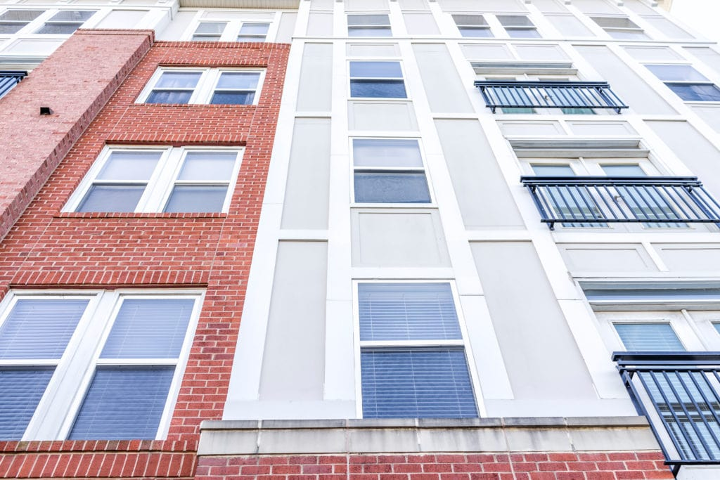 A close up shot of a mid rise condo in Virginia. Brick and concrete siding with white trim and windows, some windows with black safety rails.