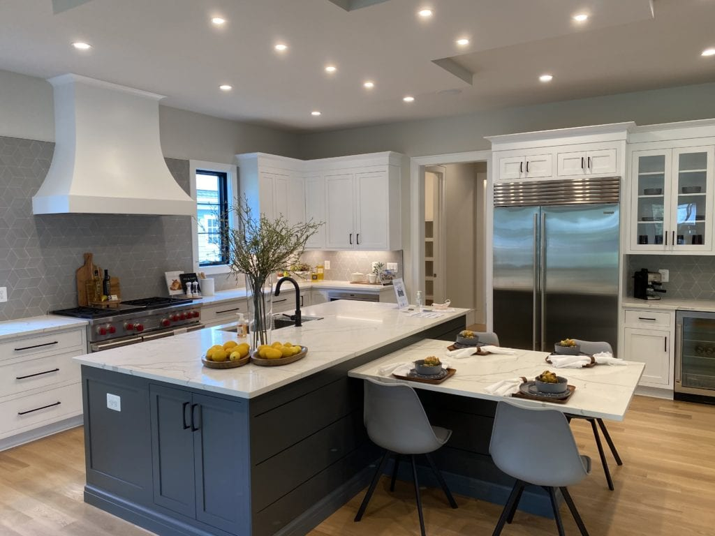 A large luxury kitchen, the bar has a small built in table coming off it, stainless steel appliances, light wood floors, white cabinets with dark hardware.