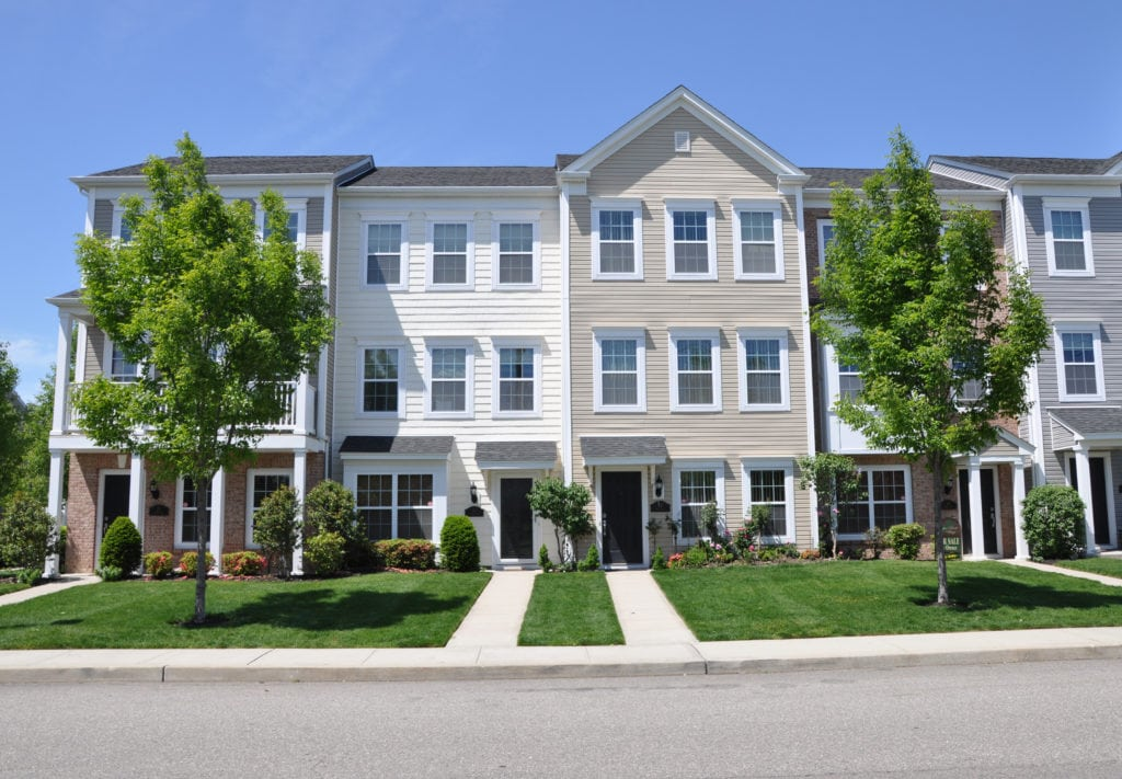 A row of new townhomes, with well manicured yards and two green trees. Black roofs over the towhomes and the awnings over the doors.