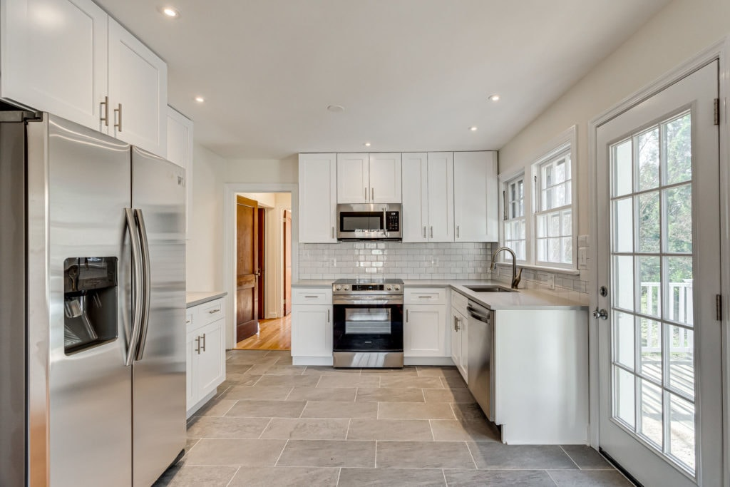 A newly renovated kitchen in 2020, white cabinets, stainless appliances and a subway tile backsplash.