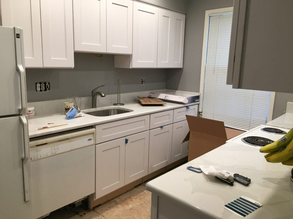 A kitchen mid renovation. White cabinets, gray paint and white quartz counters with gray swirls.