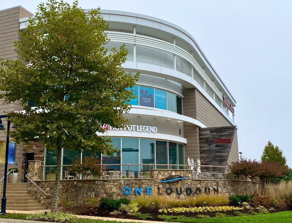 """A glass enclosed building behind a sign entrance to the Ashburn Town Center named """"One Loudoun""""."""