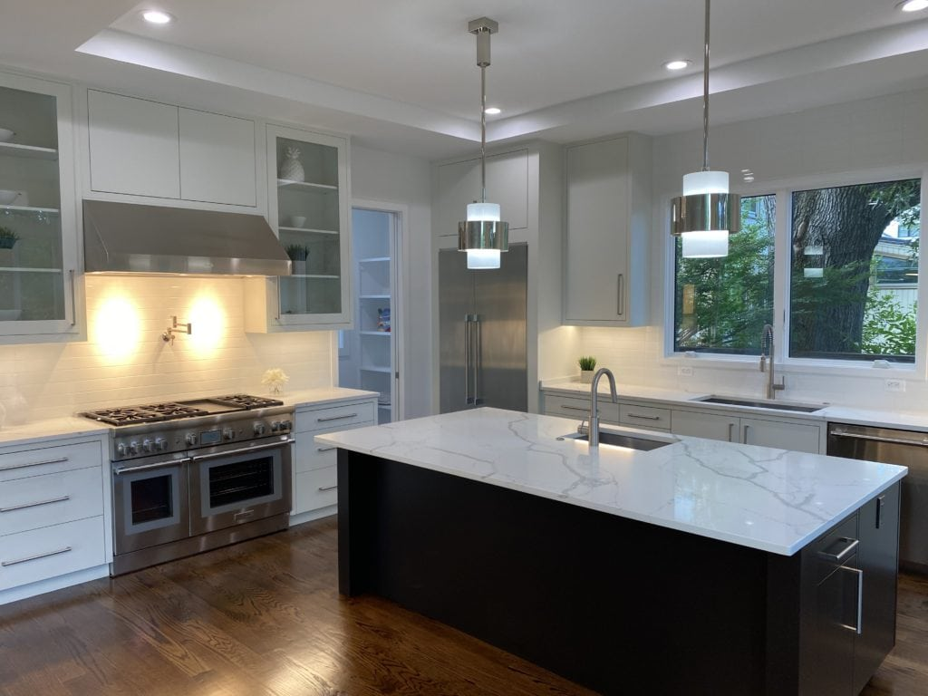 A white kitchen with marble counters, high end stainless appliances and thick wood floors.