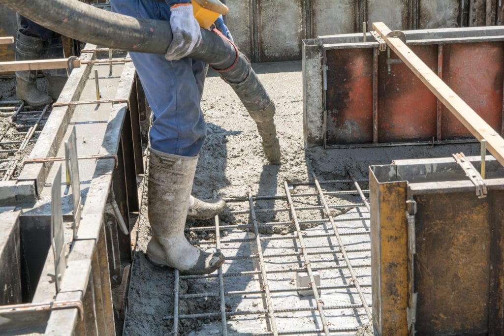 Concrete is being poured from a large hose into a home's foundation. Metal concrete forms can be seen nearby.