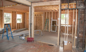 Interior of a home being renovated. Just framing is shown, drywall, electrical and plumbing have been removed. This is a home flip.