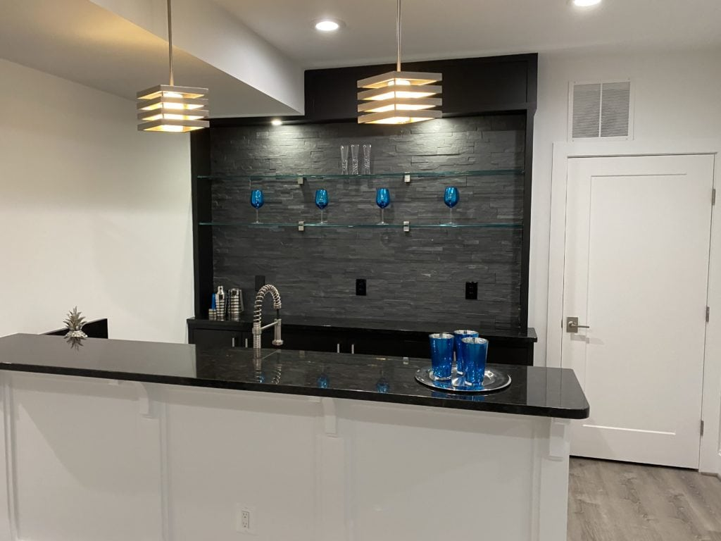 A basement bar with funky lights, dark counters and stone backsplash.