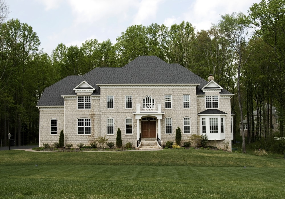 A new home with light colored brick and a large green yard.
