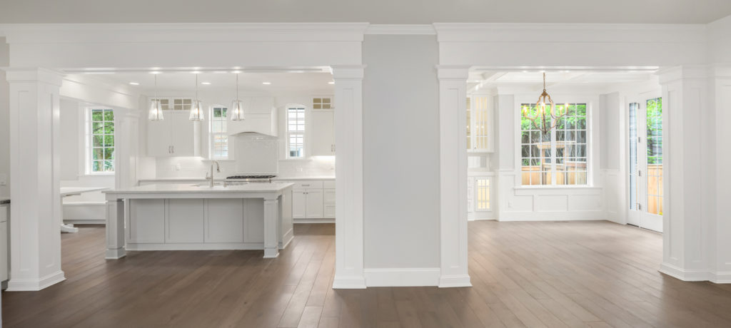 A new kitchen and breakfast area are shown. Mostly white finishes and a large kitchen island.