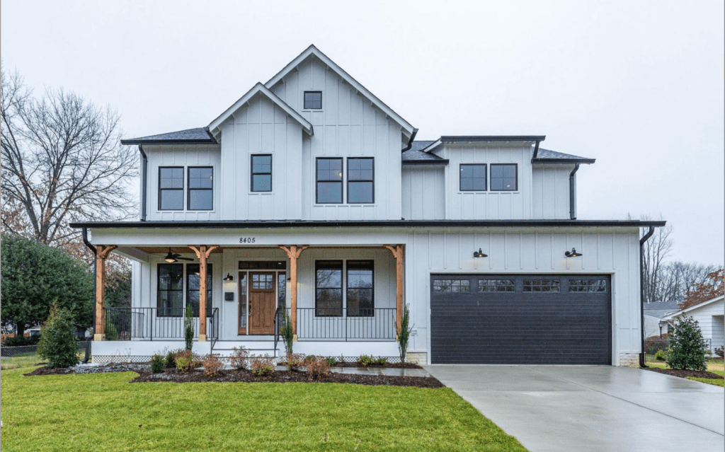A new construction home in with a modern farmhouse style, white siding with a bluish tint and a covered porch.