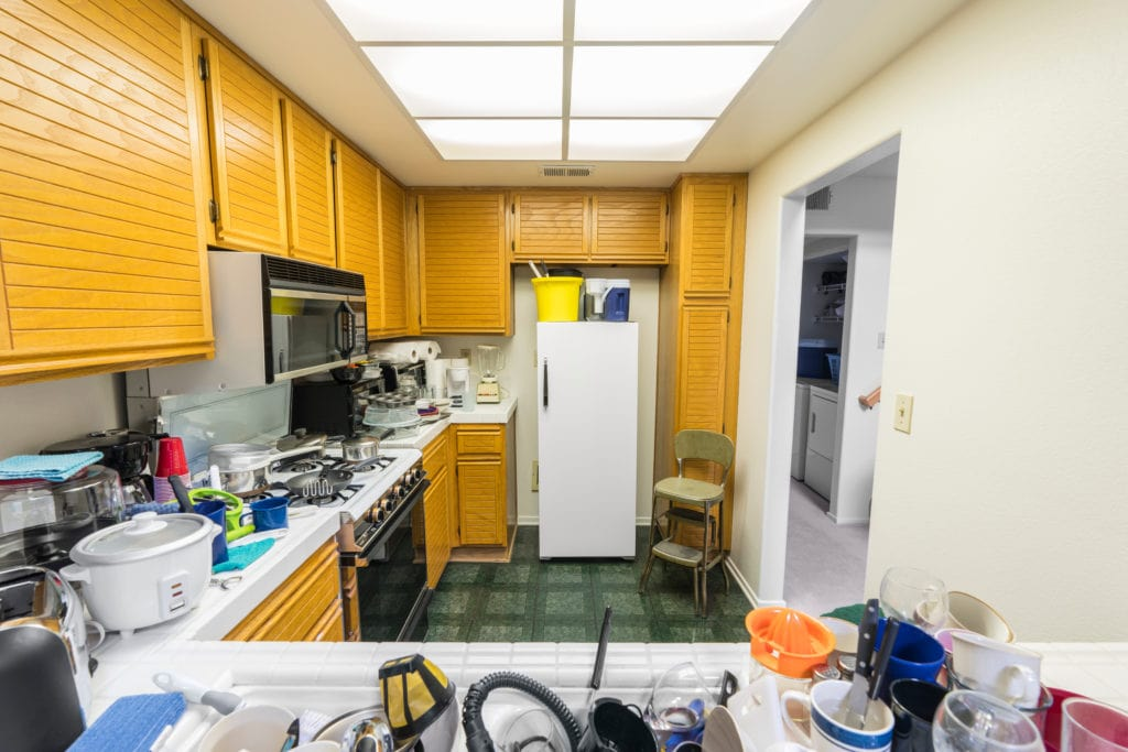 A kitchen that is cluttered with things on the counter, and above the refrigerator.