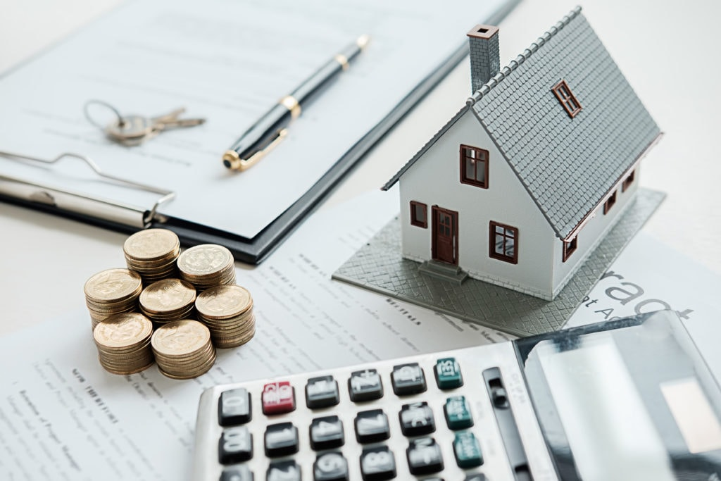 Stock photo of a calculator, contract and small home with a pen sitting on the paperwork.