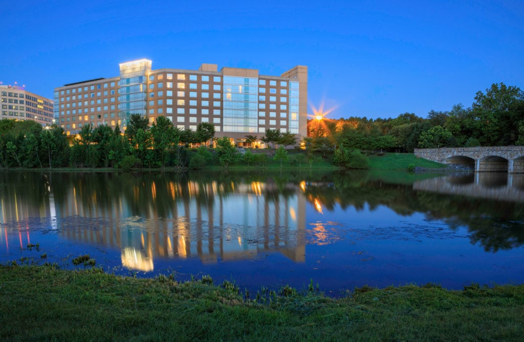 A large office building in Herndon VA is across from a small lake, with the reflection of the building in the water.