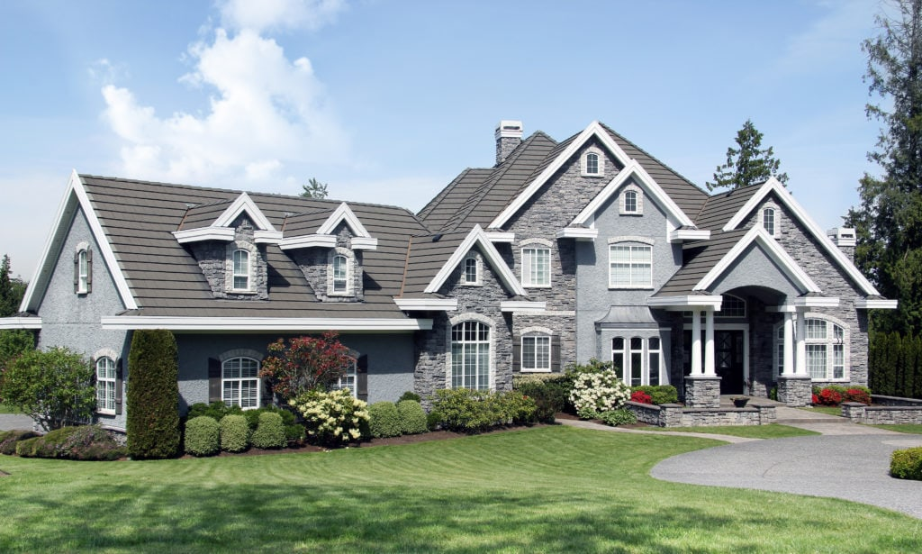 A large mansion style home with stone and small columns near the door. Manicured lawn and landscaping.