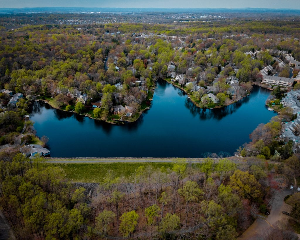 An overhead view of a man made lake in Reston, VA. The lake has three peaks and lots of shoreline. Waterfront homes can be seen.