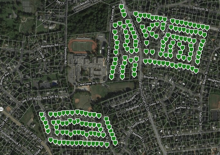 Satellite image of a neighborhood of homes, a high school is seen in the middle. Green markers mark each property.