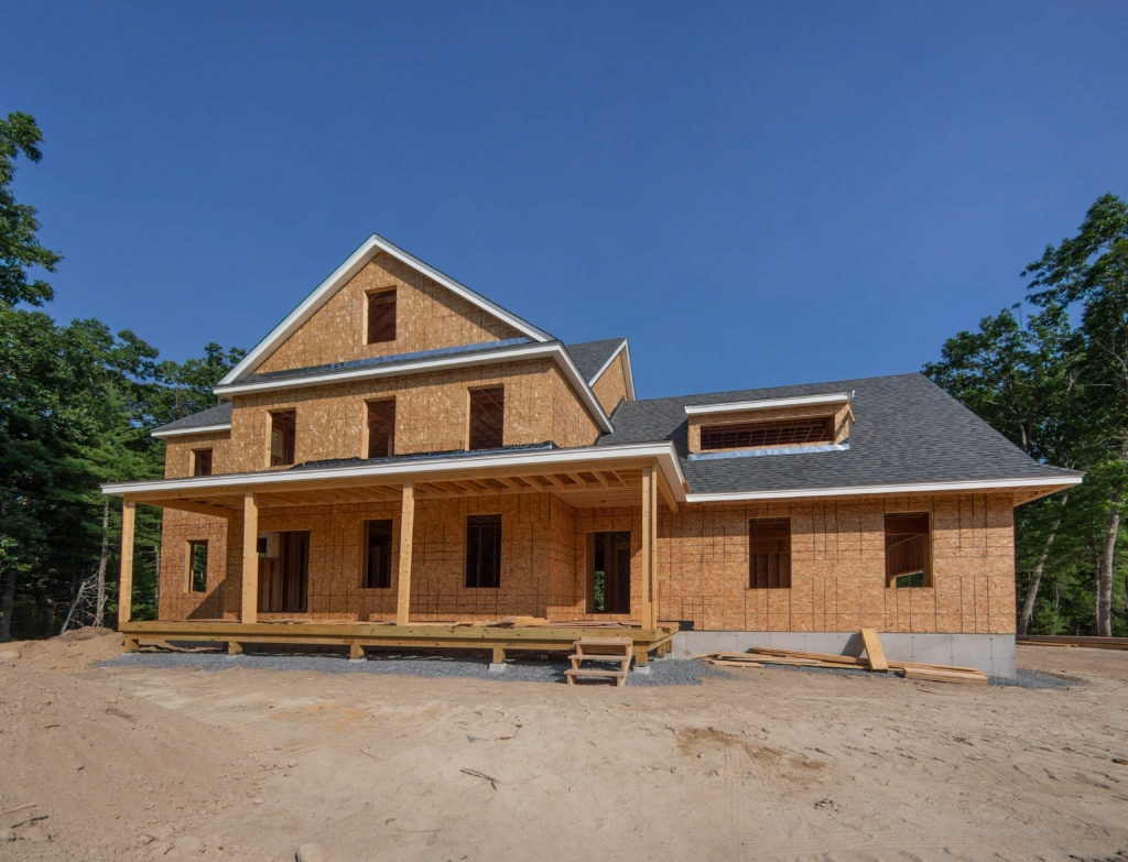 A house that has been framed and ready for siding, brand new construction home.