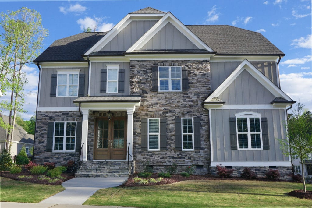 A modern colonial/farmhouse style home with a partial stone and grey plank siding.