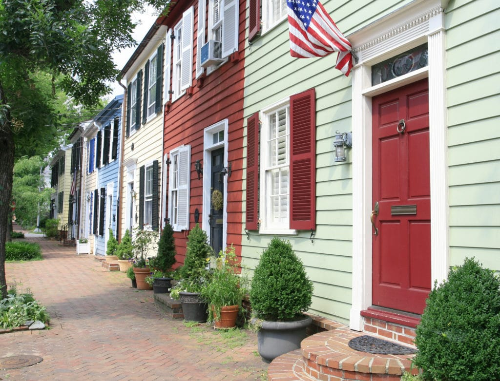 A brick sidewalk in a historic district of Alexandria, townhomes with different colors of siding and different colored doors.