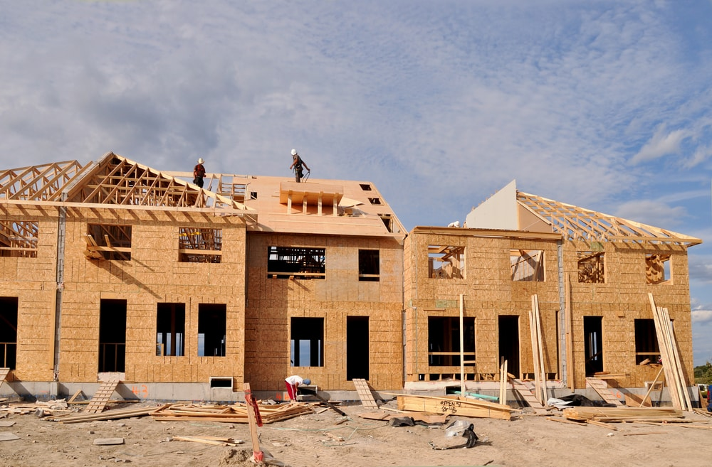A row of townhomes being built. You can see the framing and roof trusses being put in, but there is only wood and no siding yet. Dirt in the foreground.