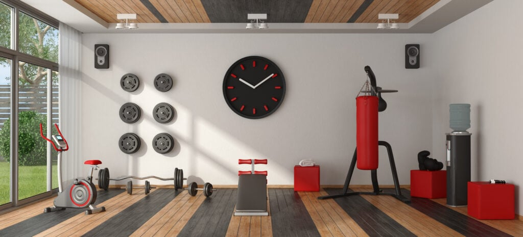 A home gym that is well organized with different equipment on the floor and hanging from the wall.