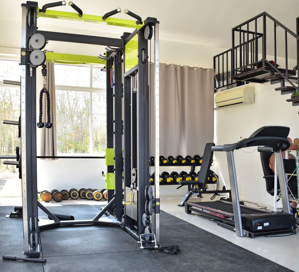 A home gym in a basement with a squat rack and lots of freeweights and a treadmill.