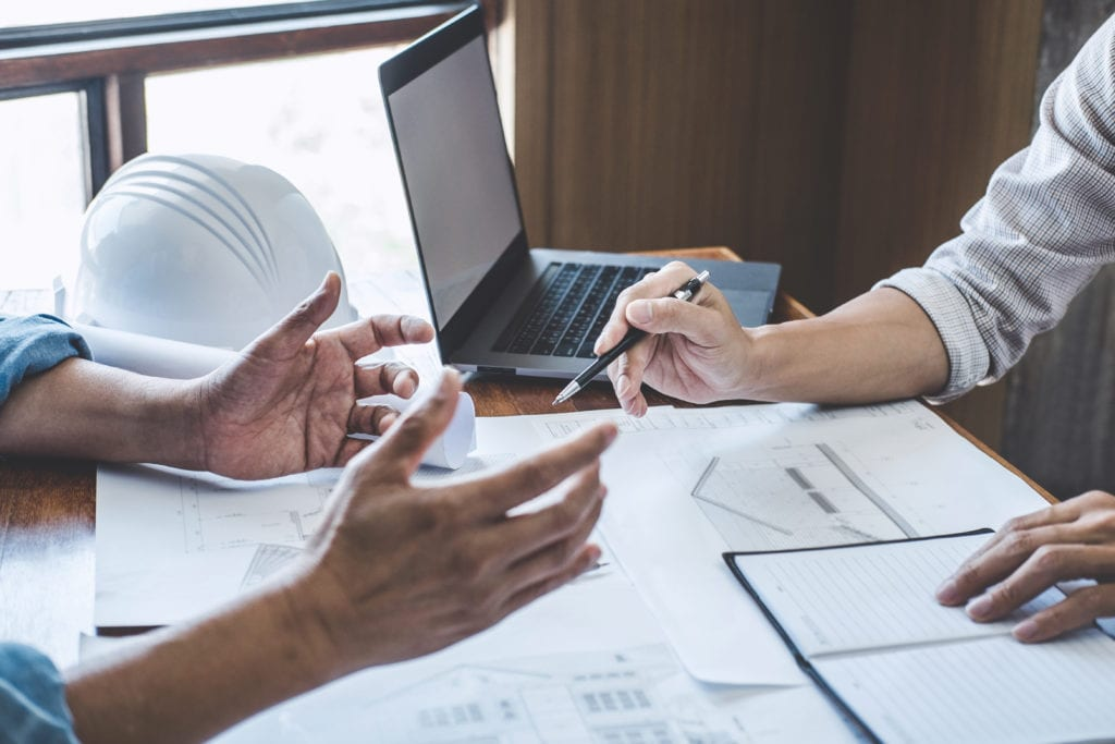 A builder and buyer converse over a new home contract.