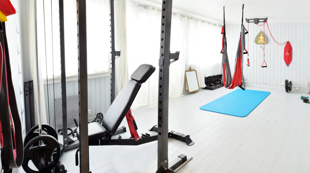 A home gym with light colored durable flooring.