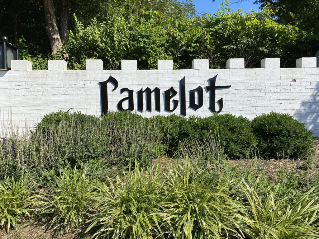 """A sign at the entrance to a neighborhood that reads """"Camelot"""" after the community. White with black lettering."""