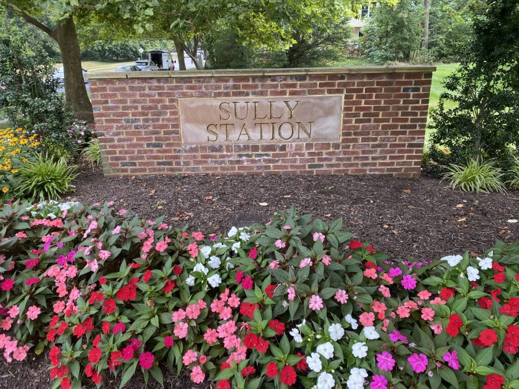 """A neighborhood sign made of brick """"Sully Station"""" and some flowers and landscaping surrounding it."""